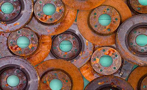 Conceptual image of overlaid old weathered rusty and corroded brake rotors from a motor car in a full frame view on a green wooden table background