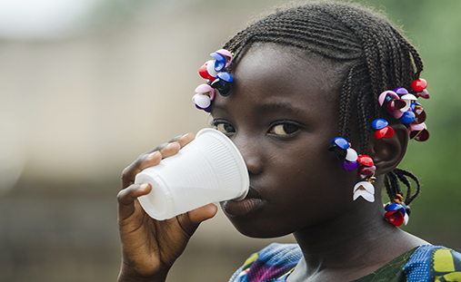 Young african girl with traditional accessories in hair drinking and looking at camera