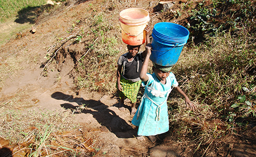 August 8, 2014-Mountain of Kilolo-Tanzania-Africa-Two unidentified girls as they climb the difficult ascent from the river with in head two buckets full of water a task that mostly only children perform
